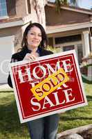 Hispanic Woman Holding Red Sold Real Estate Sign In Front of Hou