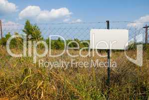 Blank white sign on a chain link fence