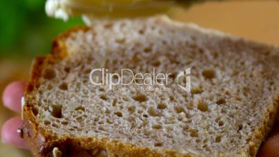 Close up of slice of bread being buttered