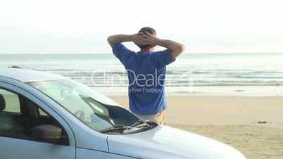 Mann entspannt neben seinem Auto am Meer