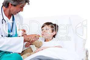 Cute little boy taking cough medicine