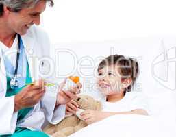 Smiling little boy taking cough medicine