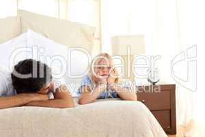 Sad little girl lying on bed with her father