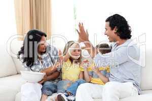 Joyful family watching TV on sofa