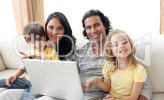 Jolly family using laptop on sofa