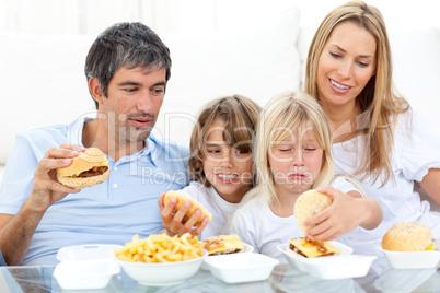 Merry family eating hamburgers