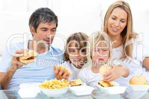 Merry family eating hamburgers