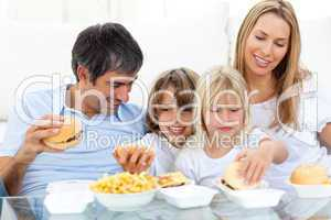 Joyful family eating hamburgers