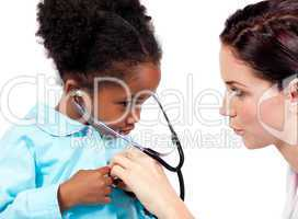 Cute little girl and her doctor playing with a stethoscope
