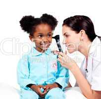 Concentrated doctor checking her patient's ears