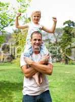 Jolly father giving his daughter piggy-back ride