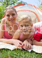 Carring mother and her little girl lying on the grass