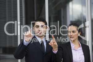 Gutaussehendes Geschäftspaar drückt auf einen virtuellen Schirm