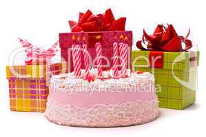 Pink pie with eight candles and gifts in boxes on a white backgr