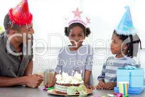 Smiling little girl and her family celebrating her birthday