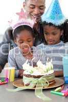 Ethnic little girl and her family celebrating her birthday