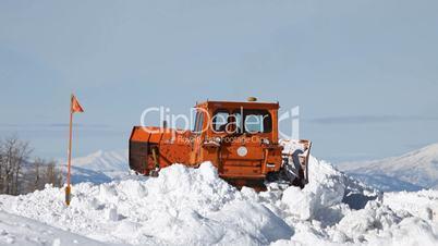 Snow plow caterpillar backing in snow