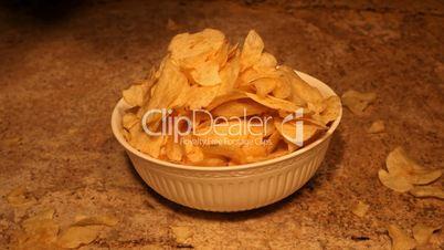 Potato chips dropping into bowl reverse