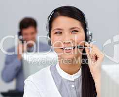 Youg asian businesswoman with headset on at her desk