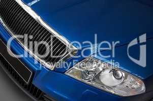 headlight and grate of radiator on a dark blue car