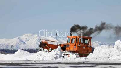 Snow plow cleaning mountain road