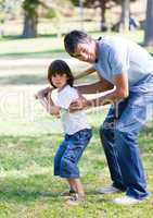 Smiling father teaching baseball to his son