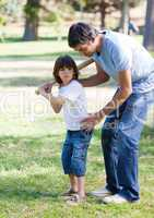 Confident father teaching baseball to his son