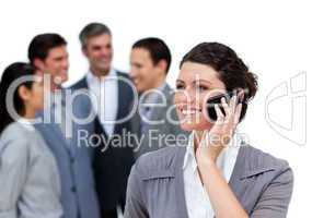 Caucasian woman talking on phone in front of her team
