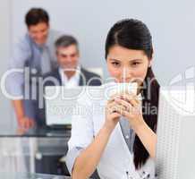 Brunette woman drinking coffee in the office