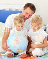 Adorable children and their father looking at a terrestrial glob