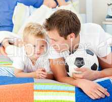 Attentive father and his son playing with a soccer ball