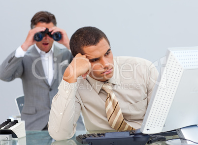 Young businessman getting bored and his manager looking through