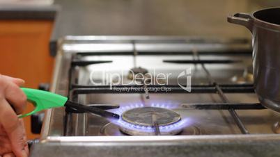 woman lights gas and puts pan on gas cooker.