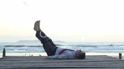 Geschäftsmann macht Fitnessübungen am Meer
