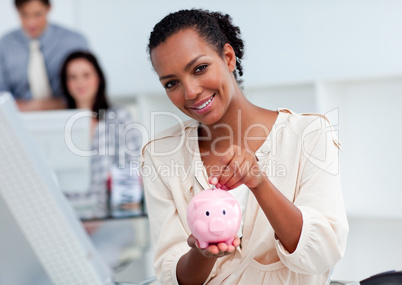Confident businesswoman saving money in a piggy-bank
