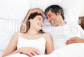 Enamored couple hugging lying in their bed