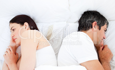 Upset couple sleeping in their bed separately