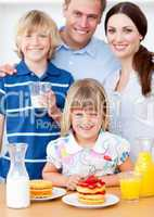 Joyful family eating breakfast in the kitchen