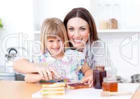 Blond little girl and her mother preparing toasts