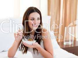 Pretty woman eating cereals sitting on bed