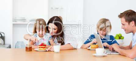 Happy family eating breakfast in the kitchen