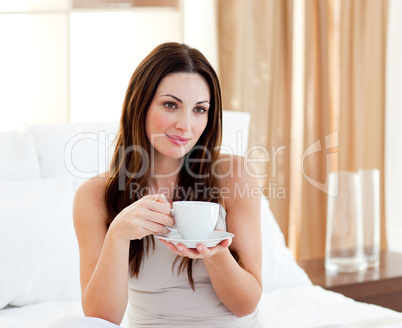 Relaxed woman drinking coffee sitting on bed
