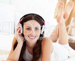 Beautiful woman listening music lying on bed
