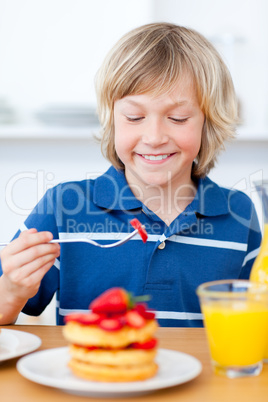 Adorable boy eating waffles with strawberries