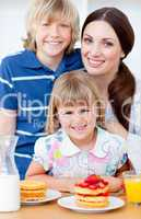 Cheerful mother and her children eating waffles with strawberrie