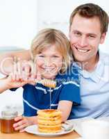 Happy boy and his father putting honey on waffles