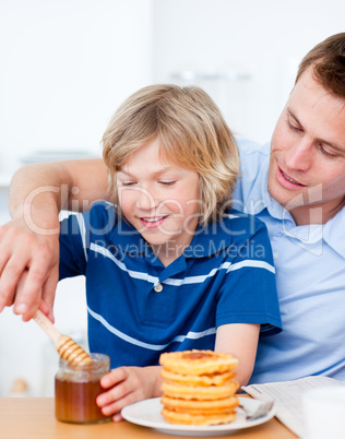 Adorable boy and his father putting honey on waffles