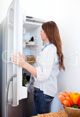 Attractive woman looking for something in the fridge