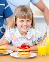 Portrait of a smiiling little girl eating waffles with strawberr