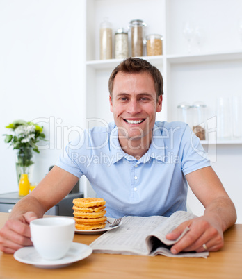 Attractive man reading a newspaper while having breakfast